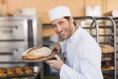 Smiling baker smelling fresh bread Royalty Free Stock Photo
