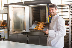 Smiling baker taking fresh croissants out of the oven Royalty Free Stock Images