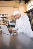Smiling baker using laptop on worktop Stock Image