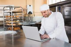 Smiling baker using laptop on worktop Royalty Free Stock Photos