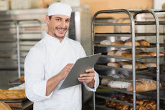 Smiling baker writing on clipboard Royalty Free Stock Photos
