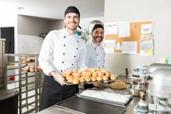 Smiling Bakers With Fresh Pastries. Portrait of male chefs preparing chouxs in bakery stock image