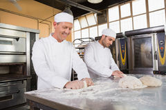 Smiling bakers kneading dough at counter Royalty Free Stock Images