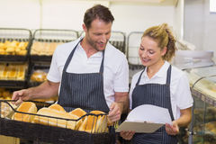 Smiling bakers looking at notepad and holding a basket with bread Royalty Free Stock Image