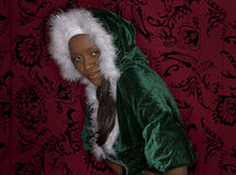 Smiling Balck woman in a holiday sweater. A beautiful young black woman in a hooded christmas sweater, restrains her excitement and works on showing an ever so stock photography