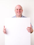 Smiling bald man holding a blank sign Stock Photography