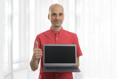 Smiling bald man with laptop Royalty Free Stock Image