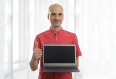 Smiling bald man with laptop. Smiling bald man presenting something on screen of laptop Royalty Free Stock Image