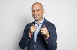 Smiling bald man pointing his fingers at you. Isolated royalty free stock images