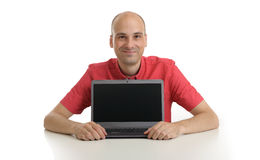 Smiling bald man presenting something on laptop Stock Photography