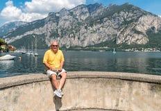 Smiling Bald mature man sitting on the shore of Como lake. Stock Photo