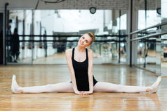 Smiling ballerina doing splits Stock Photo