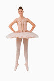 Smiling ballerina standing on her tiptoes. Against a white background Stock Images