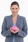 Smiling bank clerk holding piggy bank Stock Photography