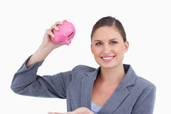 Smiling bank clerk with piggy bank in her hand Royalty Free Stock Photo