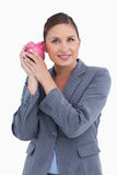 Smiling bank clerk shaking piggy bank Royalty Free Stock Photos