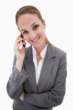 Smiling bank employee on her cellphone Royalty Free Stock Images