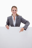 Smiling bank employee pointing down at blank sign Royalty Free Stock Image