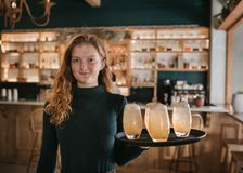 Smiling bar waitress holding a tray of drinks. Portrait of a smiling young waitress carrying a tray of drinks while working in a bar in the evening stock photography