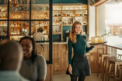 Smiling bar waitress standing with a tray of drinks royalty free stock photography