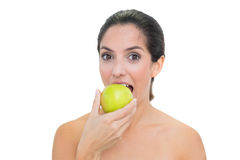 Smiling bare brunette eating green apple Stock Photos