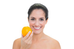 Smiling bare brunette holding orange Royalty Free Stock Images
