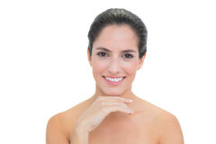 Smiling bare brunette touching her chin Stock Photo