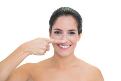 Smiling bare brunette touching her nose Royalty Free Stock Photo