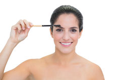 Smiling bare brunette using eyebrow brush Stock Images