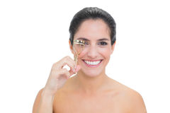 Smiling bare brunette using eyelash curler Royalty Free Stock Photo