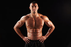 Smiling bare chested male body builder with hands on hips Stock Images