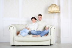 Smiling barefoot husband and wife sits on white sofa Stock Photos