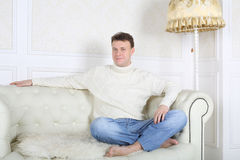 Smiling barefoot man in white sweater sits on white sofa Royalty Free Stock Images