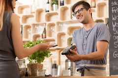 Smiling barista with costumer paying by card stock images