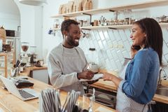 Smiling barista dictating her colleague list of necessary supplies. List of necessities. Cheerful young women dictating the list of necessary supplies, having to Stock Image