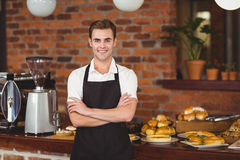 Smiling barista in front of counter with arms crossed Stock Photo