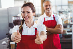Smiling barista gesturing thumbs up with colleague behind Royalty Free Stock Images