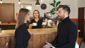 Smiling Barista girl serves to a young couple a Cup of coffee in a coffee shop. stock video