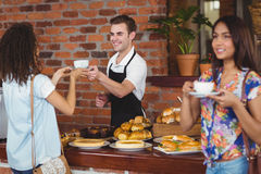 Smiling barista giving coffee to pretty customer. At coffee shop Royalty Free Stock Images