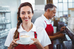 Smiling barista holding a cup of coffee with colleague behind Stock Photos