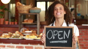 Smiling barista holding an open signboard