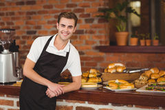Smiling barista leaning against counter Royalty Free Stock Photography