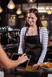 Smiling barista looking at tablet while woman is ordering Stock Photography