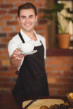 Smiling barista offering cup of coffee to camera Royalty Free Stock Photos