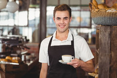 Smiling barista offering cup of coffee to camera Stock Photos