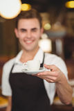 Smiling barista offering cup of coffee to camera Royalty Free Stock Photography