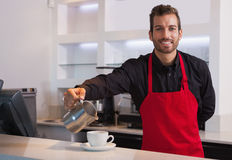 Smiling barista pouring milk into cup of coffee looking at camera Stock Photo