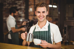 Smiling barista pouring milk in a cup Stock Images