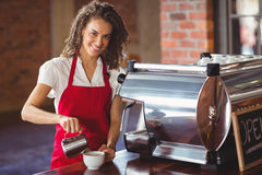 Smiling barista pouring milk in a cup Stock Photos