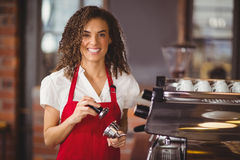 A smiling barista pressing coffee Stock Photography